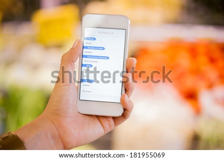 Closeup of a woman's hand holding a smart phone with a shopping list at a grocery store - stock photo