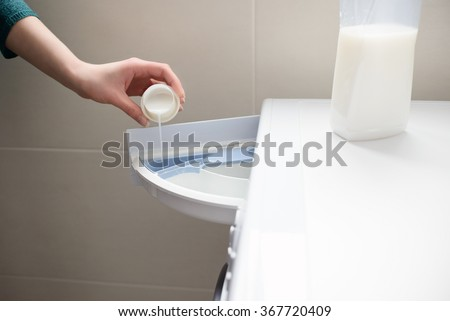 Closeup of a woman's hand pouring liquid fabric softener to the washing machine - stock photo