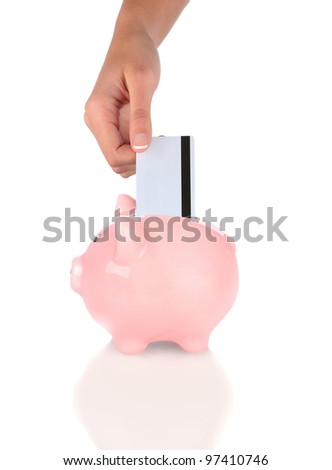 Closeup of a woman's hand putting a credit card into a piggy bank. Vertical format over white. - stock photo