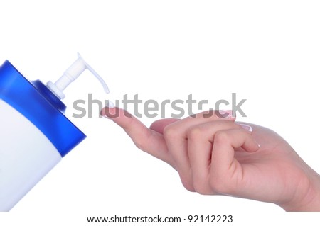 Closeup of a woman's hand with a dollop of lotion on one finger. Horizontal format over a white background.