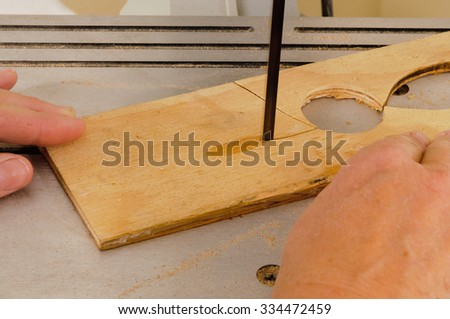 Closeup of a woman's hands working with a band-saw to cut an intricate shape in a piece of plywood - stock photo