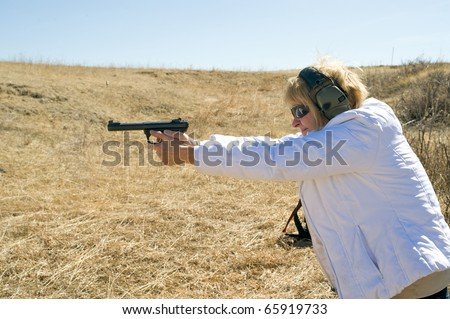 Closeup of a woman taking target practice at a shooting range. - stock photo