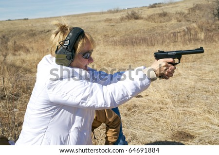 Closeup of a woman taking target practice with a pistol at a shooting range. - stock photo