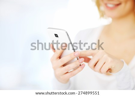 Closeup of a woman using smartphone at home - stock photo