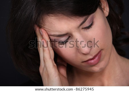 Closeup of a woman with a headache - stock photo