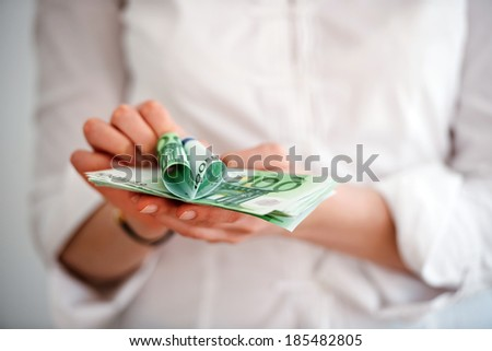 Closeup of a women hand holding Euro banknotes and a heart made of one hundred euro bill - shallow depth of field to emphasize the attention to the heart - stock photo