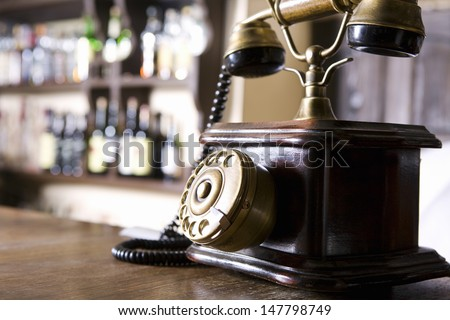 Closeup of a wood and brass antique dial telephone on bar counter - stock photo