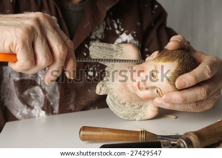 closeup of a wood sculptor hands - stock photo