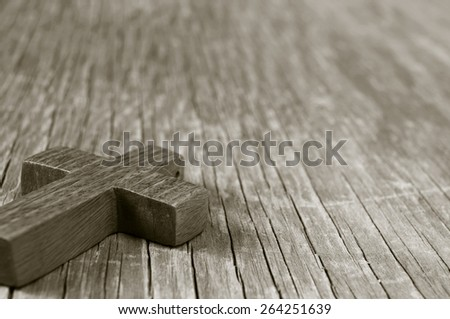 closeup of a wooden Christian cross on a rustic wooden surface, in sepia toning - stock photo