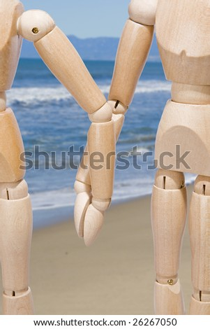 Closeup of a wooden couple holding hands on the beach - stock photo