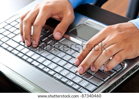 Closeup of a worker using a laptop computer - stock photo