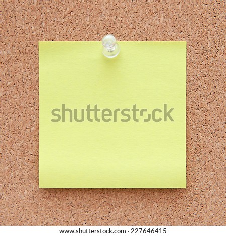 Closeup of a yellow note paper on a corkboard