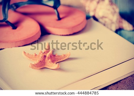 closeup of a yellow starfish and a pair of colorful orange flip-flops on a book, with a conch in the background, and a retro effect - stock photo