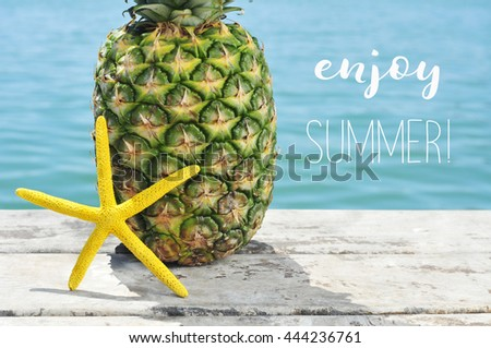 closeup of a yellow starfish and a pineapple on a weathered wooden pier with the ocean in the background and the text enjoy summer - stock photo