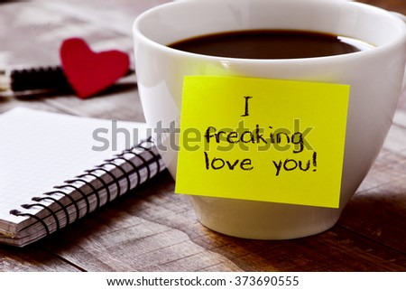 closeup of a yellow sticky note with the text I freaking love you attached to a cup of coffee, on a rustic wooden table, next to a notebook, a red heart and a pen - stock photo