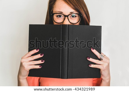 Closeup of a young and caucasian woman who hides her face with a book - lifestyle and people concept - stock photo