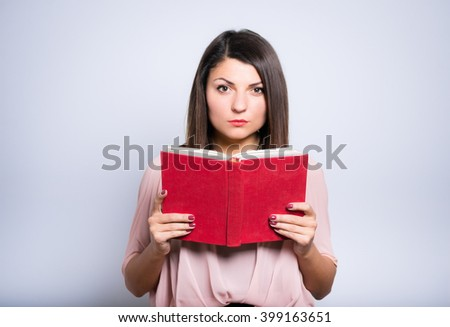 closeup of a young beautiful woman is reading a book with glasses - stock photo