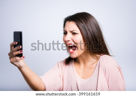 closeup of a young beautiful woman screaming on a smartphone