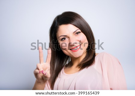 closeup of a young beautiful woman shows gesture of victory, peace