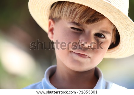Closeup of a young boy in a straw hat - stock photo