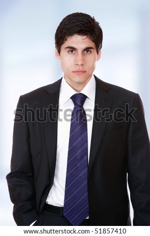 Closeup of a young business man standing in a light and modern background.