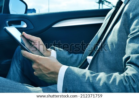 closeup of a young businessman using a tablet in a car - stock photo