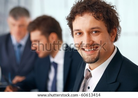 Closeup of a young businessman with his colleagues at the background. - stock photo