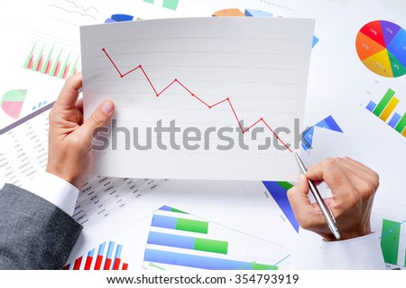 closeup of a young caucasian businessman at his office desk full of graphs and charts observing a chart with a downward trend - stock photo