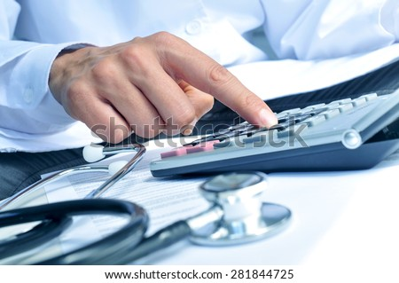 closeup of a young caucasian healthcare professional wearing a white coat calculates on an electronic calculator - stock photo