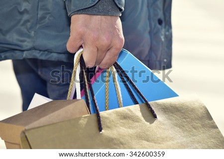 closeup of a young caucasian man carrying some different paper shopping bags in the street - stock photo
