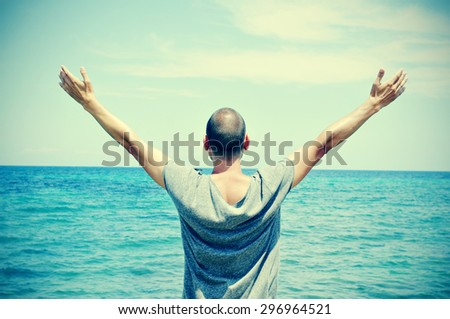 closeup of a young caucasian man seen from behind with his arms in the air in front of the ocean, feeling free, with a slight vignette added - stock photo