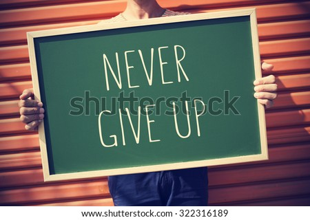 closeup of a young caucasian man showing a chalkboard with the text never give up, with a slight vignette added - stock photo