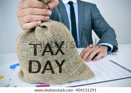 closeup of a young caucasian man sitting at his office desk holding a burlap money bag with the text tax day written in it - stock photo