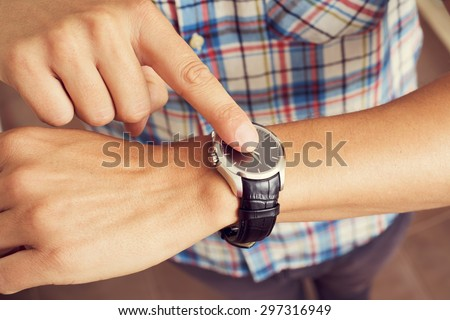 closeup of a young caucasian man tapping his forefinger on his wristwatch  - stock photo