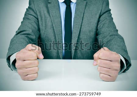 closeup of a young caucasian man wearing a gray suit banging his fists on his office desk - stock photo