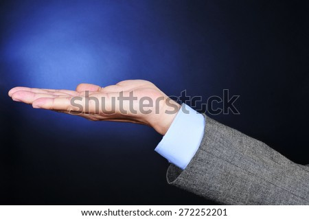 closeup of a young caucasian man wearing a gray suit with his hand open, as begging or showing or holding something, on a blue lighted black background - stock photo