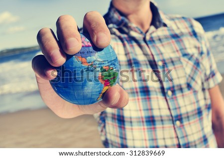 closeup of a young caucasian man with a world globe in his hand - stock photo