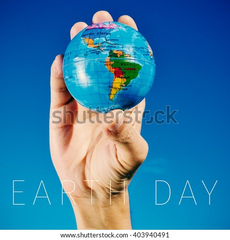 closeup of a young caucasian man with a world globe in his hand and the text earth day - stock photo