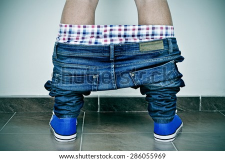 closeup of a young caucasian man with his denim pants and his underwear down, seen from behind - stock photo