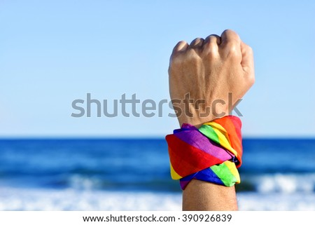 closeup of a young caucasian man with his fist raised to the sky and a kerchief patterned as the rainbow flag tied in it, with the ocean in the background - stock photo