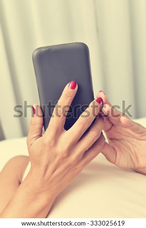 closeup of a young caucasian woman in bed using a smartphone - stock photo