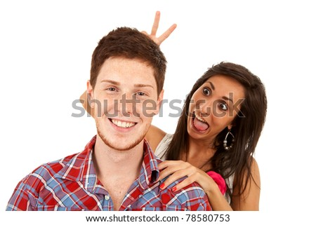 closeup of a young couple - woman goofing around behind her boyfriend - stock photo