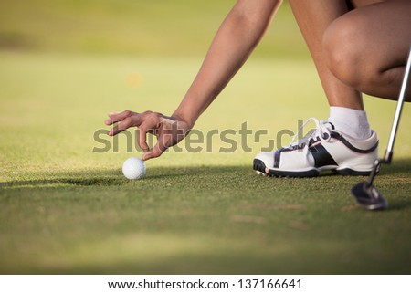 Closeup of a young female golfer pushing the ball with her finger - stock photo