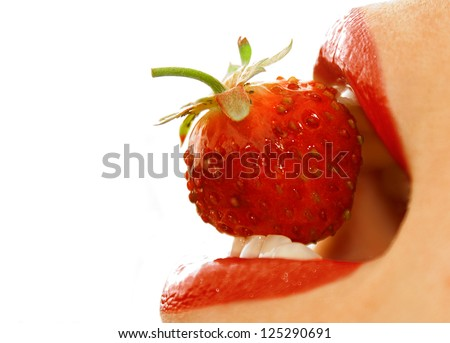 Closeup of a young girl mouth with a strawberry over white background with selective focus