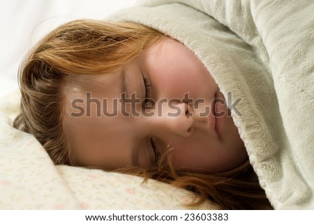 Closeup of a young girl sleeping with a warm blanket over her