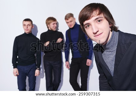 Closeup of a young male peeking into a camera, his fiends at background standing talking - stock photo