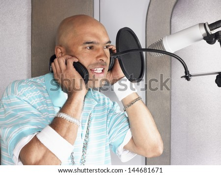 Closeup of a young male singer recording a track in a studio - stock photo