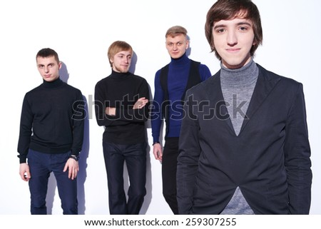 Closeup of a young male standing relaxed looking at camera, his fiends at background standing talking - stock photo