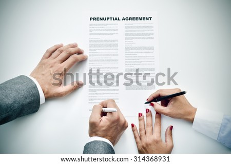 closeup of a young man an a young woman signing a prenuptial agreement - stock photo