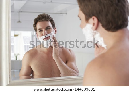Closeup of a young man applying shaving cream - stock photo